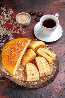 Вид сверху вкусной сладкой выпечки, нарезанной кусочками с чаем на темном столе