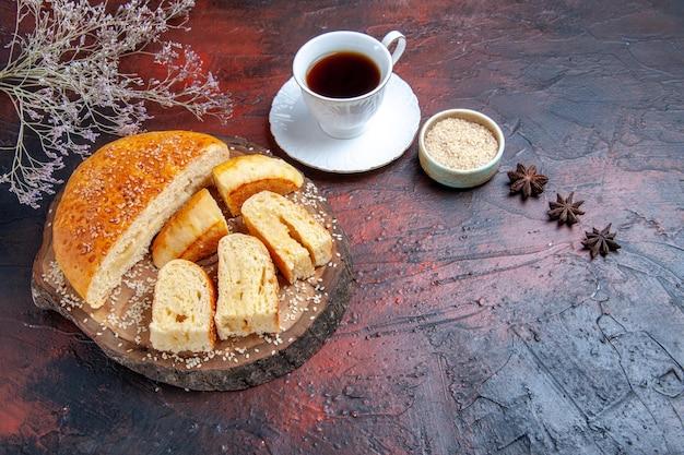 Вид сверху вкусной сладкой выпечки, нарезанной кусочками с чаем на темной поверхности