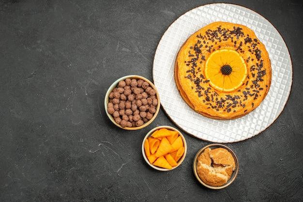 Top view tasty sweet pie with orange slices on dark grey desk sweet pie dessert tea biscuit cake sugar