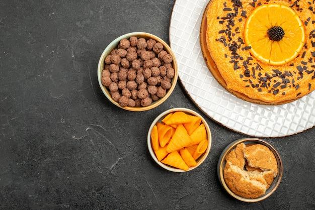 ダークグレーの机の上にオレンジのスライスが付いたおいしい甘いパイの上面図甘いパイのデザートティービスケットケーキシュガー
