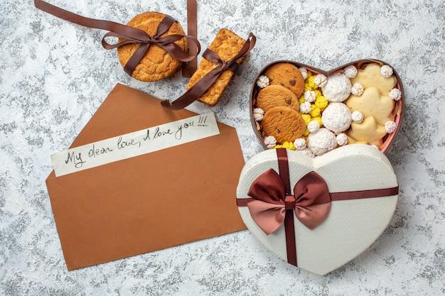 Вид сверху вкусные сладости, печенье, печенье и конфеты внутри коробки в форме сердца на белом фоне, сахарный чай, сладкий вкусный торт