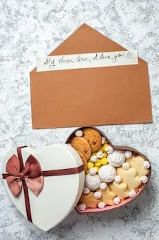 Vista dall'alto gustosi dolci biscotti biscotti e caramelle all'interno di una scatola a forma di cuore sulla superficie bianca torta di zucchero tè dolce yummy cake