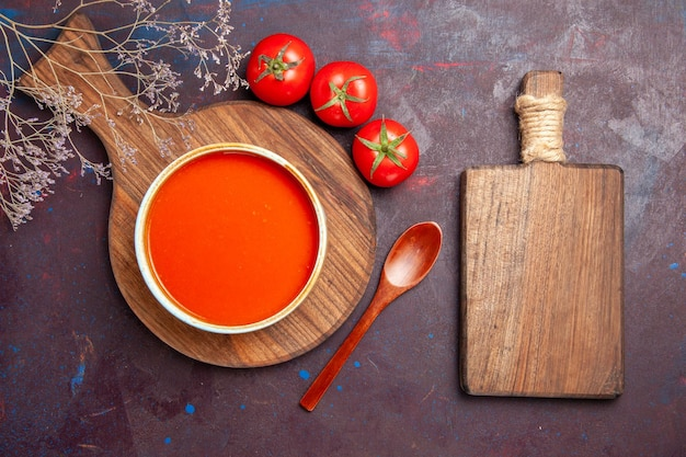 Top view of tasty tomato soup with fresh tomatoes on dark