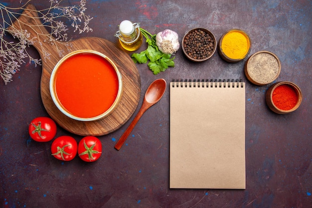 Top view of tasty tomato soup with seasonings and fresh tomatoes on dark