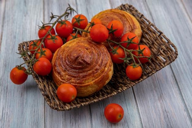 Vista dall'alto della gustosa pasticceria azerbaigiana tradizionale gogal su un vassoio di vimini con pomodori a grappolo su un fondo di legno grigio