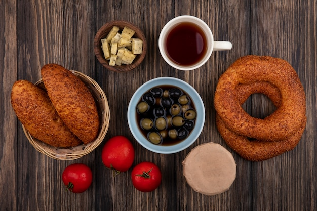 Vista dall'alto di gustosi bagel turchi con polpette su un secchio con olive su una ciotola con una tazza di tè e pomodori isolati su uno sfondo di legno