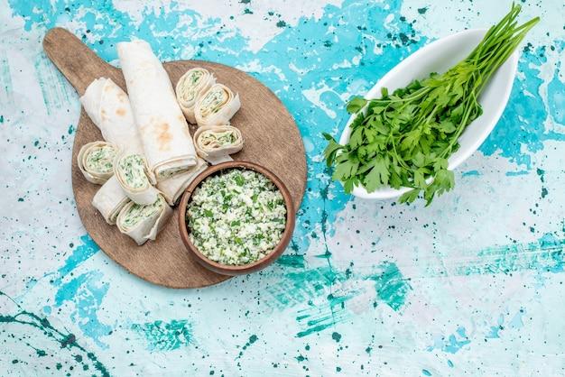 Вид сверху вкусные овощные рулеты целиком и нарезанные с зеленью и салатом из капусты на ярко-синем столе еда рулет овощной обед