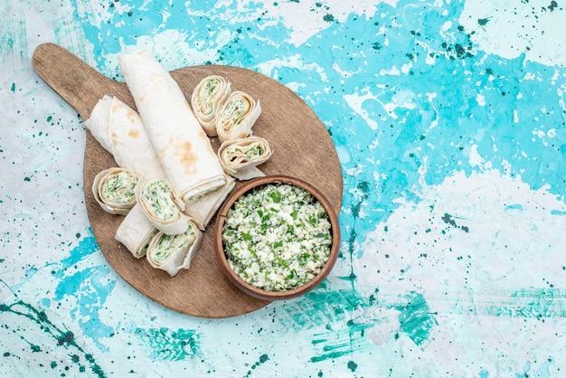 Вид сверху вкусные овощные рулеты целиком и нарезанные с зеленью и салатом из капусты на ярко-синем столе еда рулет овощная закуска обед