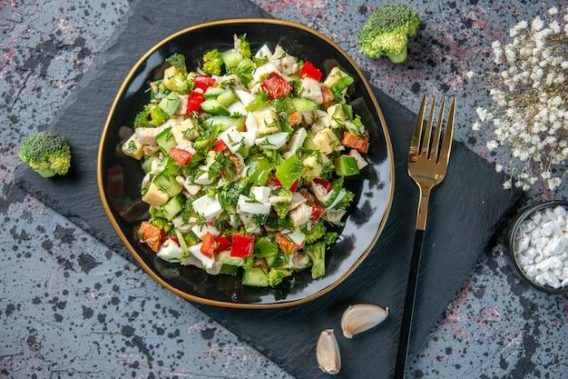 上面図おいしい野菜サラダは、暗い背景のプレート内のキュウリチーズとトマトで構成されています健康ダイエットカラーランチ食事料理料理