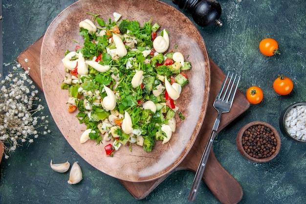 トップビューダークブルーの背景にプレート内のおいしい野菜サラダ料理ディナー食事ランチ健康フィットキッチンレストランの色