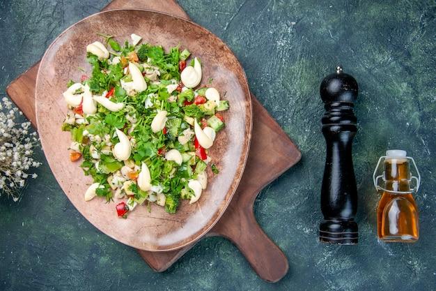 Вид сверху вкусный овощной салат внутри тарелки на синем фоне кухня ужин еда обед здоровье подходит цвет ресторана