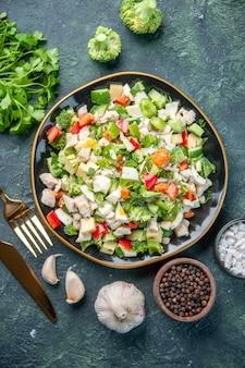 暗い背景の料理レストラン新鮮な食事色健康ランチダイエットのカトラリーとプレート内のおいしい野菜サラダの上面図