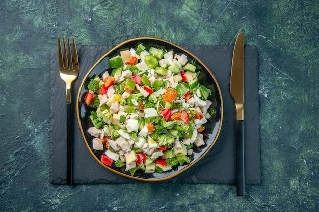 Vista dall'alto gustosa insalata di verdure all'interno della piastra con forchetta su sfondo scuro cucina ristorante fresco pasto colore salute pranzo cibo dieta