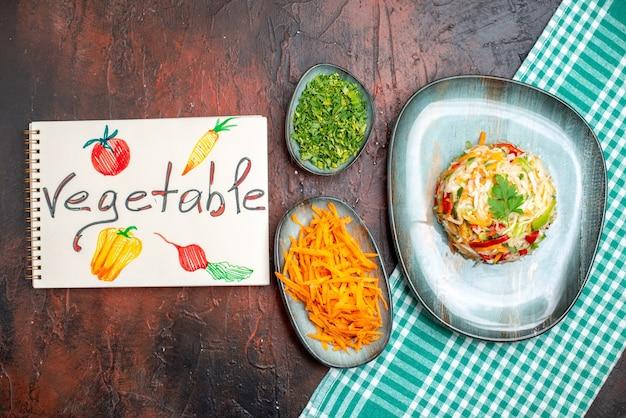 Vista dall'alto gustosa insalata di verdure all'interno del piatto con verdure e carote affettate sul tavolo scuro