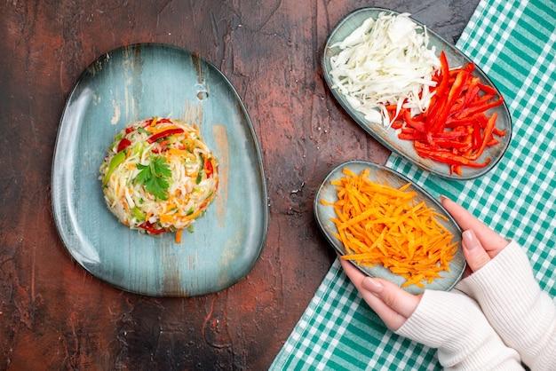 暗いテーブルの上にスライスしたキャベツとニンジンとプレートの内側の上面図おいしい野菜サラダ