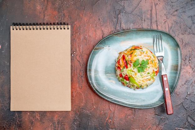 暗いテーブルの上のプレートの内側の形をした丸い形のおいしい野菜サラダの上面図