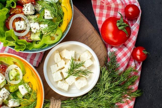 暗い背景にチーズとトマトのトップビューおいしい野菜サラダ