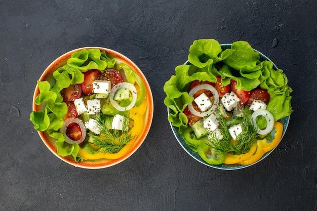暗い背景にチーズきゅうりとトマトのトップビューおいしい野菜サラダ
