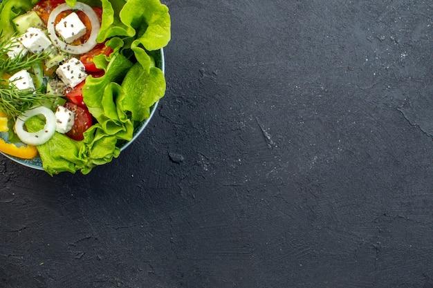 Вид сверху вкусный овощной салат с сырными огурцами и помидорами на темном фоне