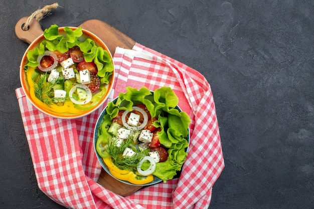 Vista dall'alto gustosa insalata di verdure con formaggio cetrioli e pomodori su sfondo scuro