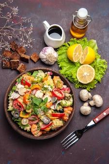 Top view of tasty vegetable salad with fresh lemon slices on dark