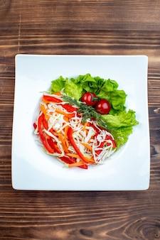 茶色の表面のプレートの内側にグリーンサラダとキャベツを添えた上面図のおいしい野菜サラダ
