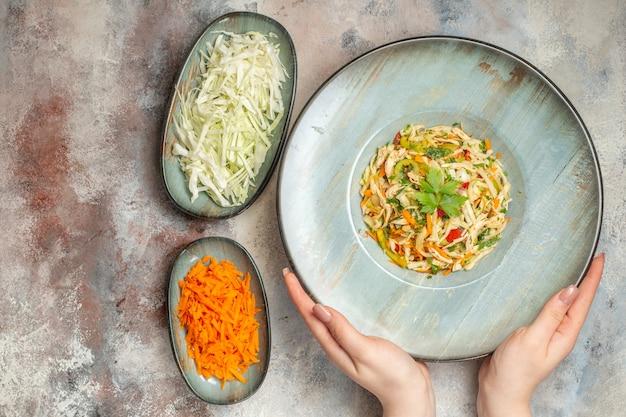 明るい背景にスライスしたニンジンとキャベツの上面図おいしい野菜サラダ