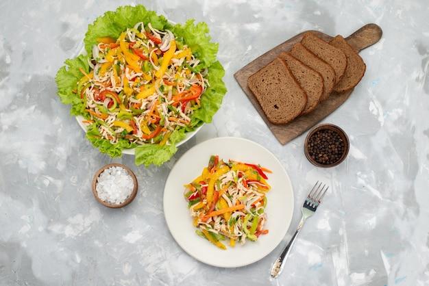 Вид сверху вкусный овощной салат с нарезанными овощами и зеленым салатом с буханками хлеба на сером, овощной салат еда еда