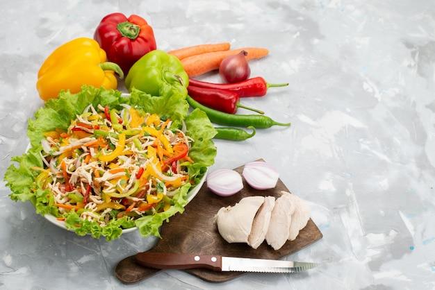 Вид сверху вкусный овощной салат с нарезанными овощами и целыми свежими овощами и сырой куриной грудкой на сером, салатная еда