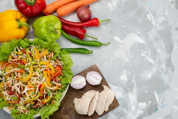 Вид сверху вкусный овощной салат с нарезанными овощами и целыми свежими овощами и сырыми куриными грудками на сером, салатная еда