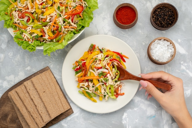 Insalata di verdure saporita di vista superiore con le verdure affettate dentro il piatto con i condimenti su pasto grigio e di verdure dell'insalata