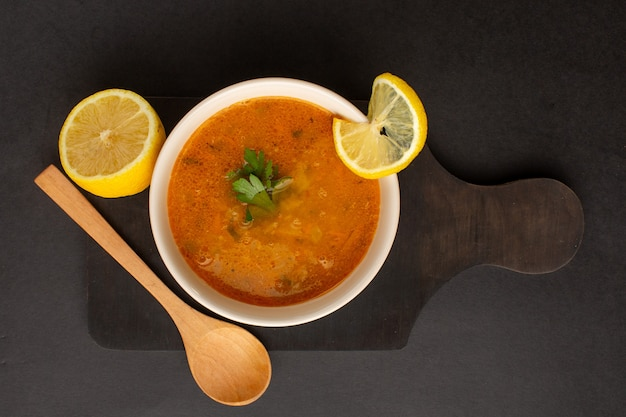Top view of tasty vegetable soup inside plate along with lemon on dark surface