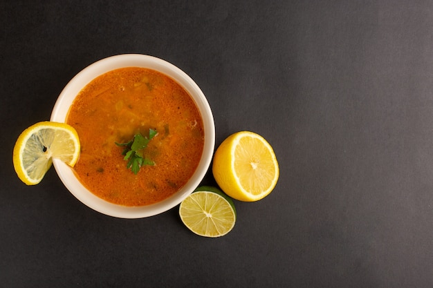 Top view of tasty vegetable soup inside plate along with lemon on the dark surface