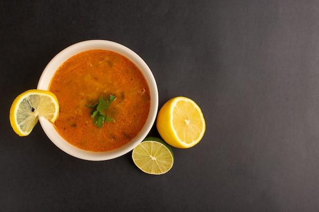 Vista dall'alto di una gustosa zuppa di verdure all'interno del piatto insieme al limone sulla superficie scura