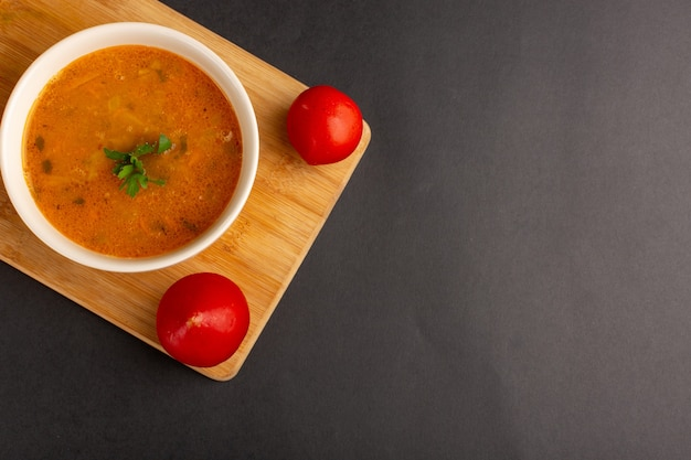 Top view of tasty vegetable soup inside plate along with tomatoes on dark surface