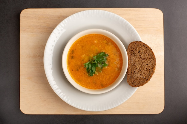 Top view of tasty vegetable soup inside plate with bread loaf on dark surface