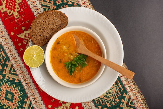 Top view of tasty vegetable soup inside plate with bread loaf and lemon on dark surface