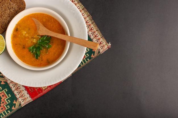 Vista dall'alto di una gustosa zuppa di verdure all'interno del piatto con pagnotta di pane e limone sulla superficie scura