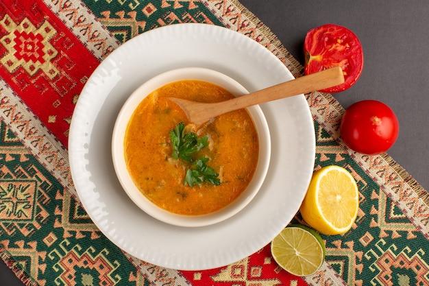Vista dall'alto di una gustosa zuppa di verdure all'interno del piatto con pomodori e limone sulla superficie scura