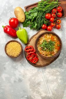 Vista dall'alto una gustosa zuppa di verdure con verdure fresche e verdi sul cibo del pasto della minestra di verdura della parete bianca