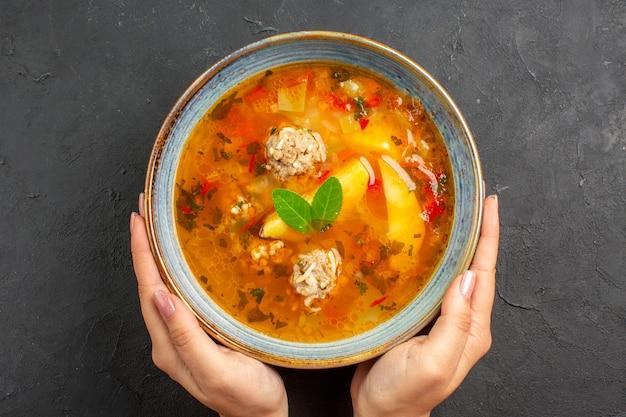ダークテーブルの皿皿の食事に肉とジャガイモを添えた上面図のおいしい野菜スープ