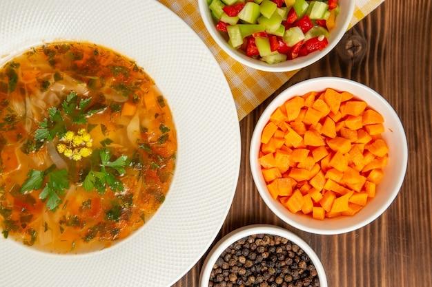 Vista dall'alto gustosa zuppa di verdure con condimenti sul pasto di condimento vegetale di zuppa di legno marrone scrivania cibo
