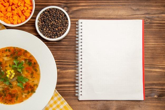 Вид сверху вкусный овощной суп с приправами на коричневом деревянном столе суп еда овощи приправы еда