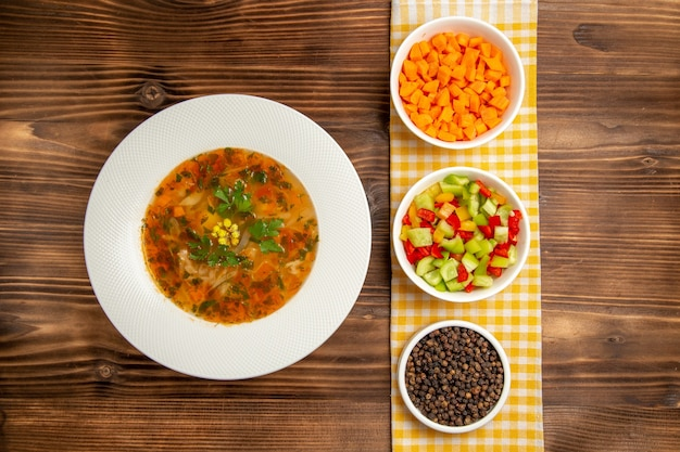 茶色の木製デスクに調味料を入れたトップビューのおいしい野菜スープスープ食品野菜調味料食事