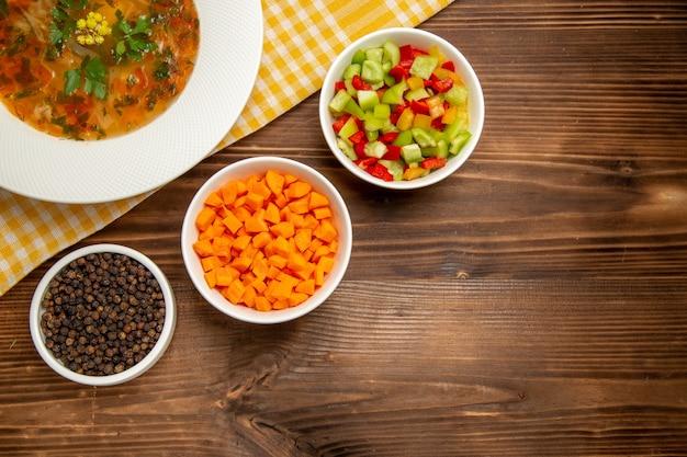 Vista dall'alto gustosa zuppa di verdure con verdure a fette su condimenti di verdure di cibo zuppa di legno marrone scrivania