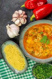 ライトグレーのテーブルにガーリックグリーンと野菜を添えたトップビューのおいしい春雨スープ