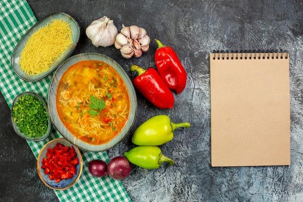 Vista dall'alto gustosa zuppa di vermicelli con aglio e verdure sul tavolo grigio chiaro