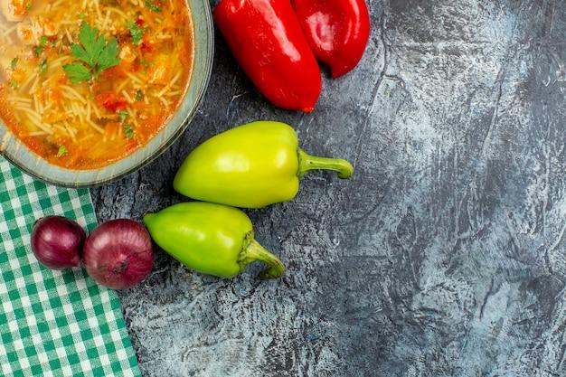 Vista dall'alto gustosa zuppa di vermicelli con aglio e verdure su un tavolo grigio chiaro
