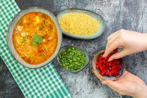 ライトグレーのテーブルに緑と生の春雨が入った上面図のおいしい春雨スープ