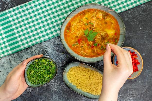 Vista dall'alto gustosa zuppa di vermicelli con verdure sul tavolo grigio chiaro
